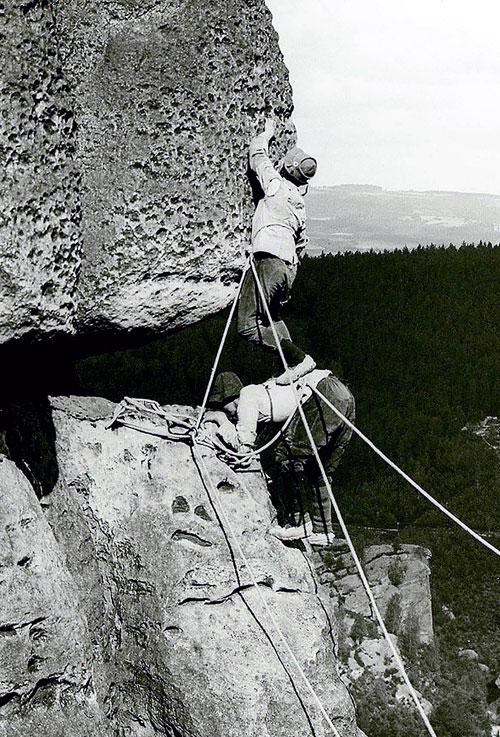 """Lezci v Českosaském Švýcarsku kolem roku 1915. Konopná lana odvážně navázaná kolem pasu, obuv s plstěnou podešví. Na obrázku zvláštní technika lezení zvaná """"stavění"""""""