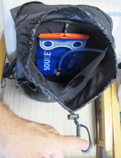 Vnitřek s instalovaným Camelbackem a očko na stahování hrdla batohu s tankou.