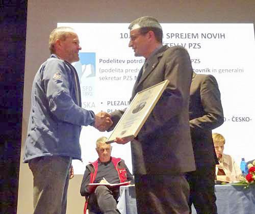 Předseda česko-slovinského alpského spolku přebírá potvrzení o členství v PZS