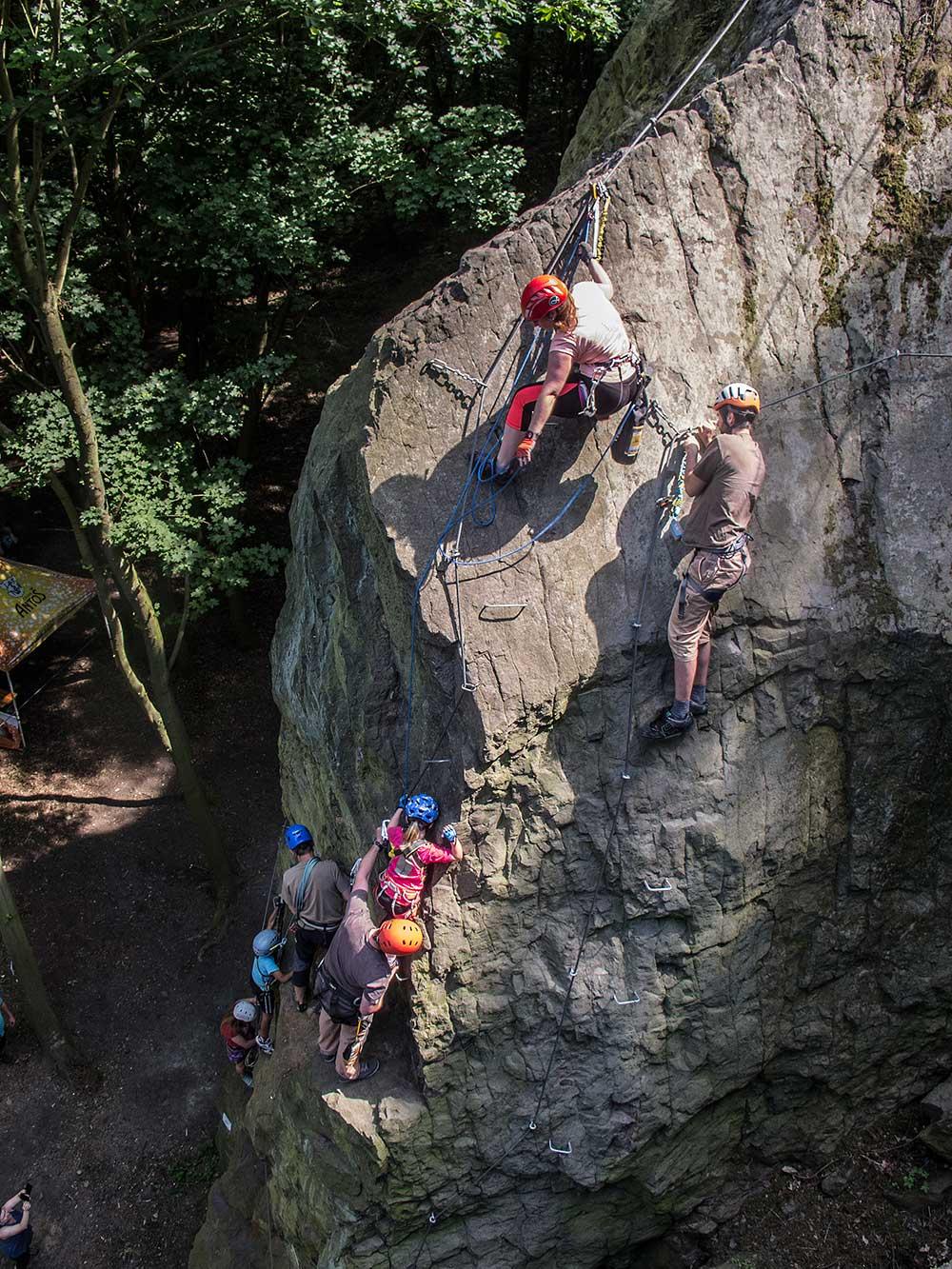 Rodina na ferratě. matka nahoře jistí dítě podporované zespodu otcem. Přihlíží lezec na vedlejším laně.
